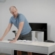 Adult Man Is Finishing an Assembly of White Desk in a Flat, Checking Openning and Closing and - VideoHive Item for Sale