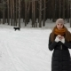 Pretty Girl in the Winter Woods Taking a Selfie. Nearby Runs a Black Dog - VideoHive Item for Sale