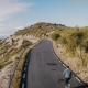 Hipster Man Rides on Skateboard on Mountain Road - VideoHive Item for Sale