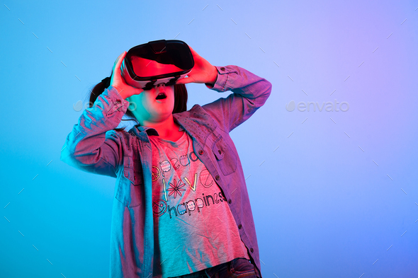 Young girl watching a movie on VR headset - Stock Photo - Images
