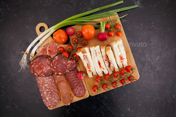 Top view of club sandwiches next to a board with appetizers - Stock Photo - Images