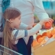 Little Daughter Choosing Fruits in Supermarket. Mom, Dad and Girl Selecting Oranges in Shopping - VideoHive Item for Sale