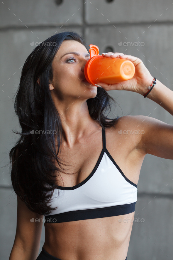 close up portrait of drinking sportswoman in gym - Stock Photo - Images