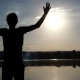 Young Man Raises Hands Happily on a Lake Bank at Sunset - VideoHive Item for Sale
