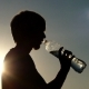 Happy Man Drinks Water From a Plastic Bottle at Sunset - VideoHive Item for Sale