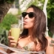 Mixed Race Young Tourist Woman Drinking Green Smoothie and Using Smartphone and Relaxing in Hammock - VideoHive Item for Sale