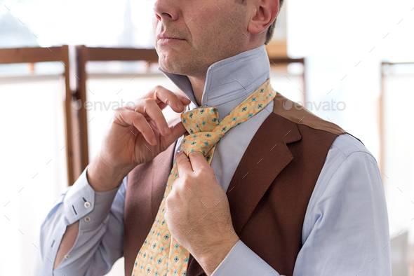Man knotting his necktie while dressing - Stock Photo - Images