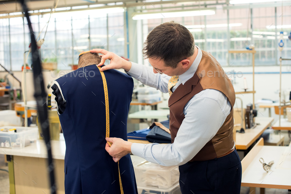 Tailor measuring jacket in his workshop - Stock Photo - Images