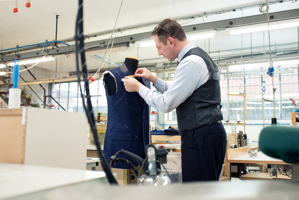 Tailor standing working on a blue jacket - Stock Photo - Images