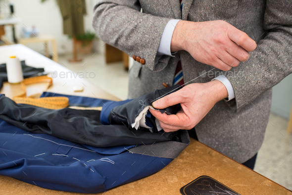 Work in progress with a tailor sewing a jacket - Stock Photo - Images