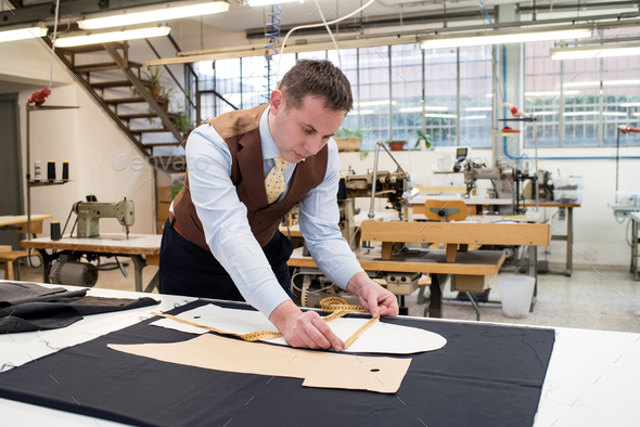 Tailor working with paper patterns on new jacket - Stock Photo - Images