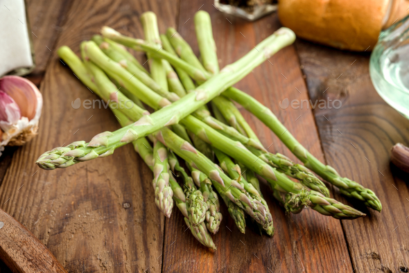 green asparagus without cooking, on rustic wood - Stock Photo - Images