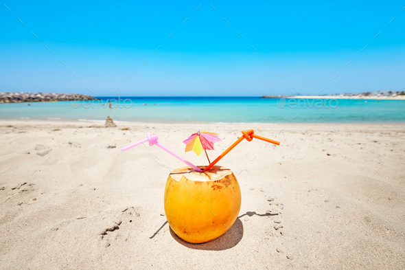 Coconut cocktail with colorful umbrella and two straws on a beac - Stock Photo - Images