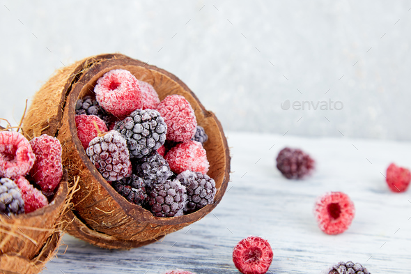Frozen black and red raspberries in coconut bowl. - Stock Photo - Images