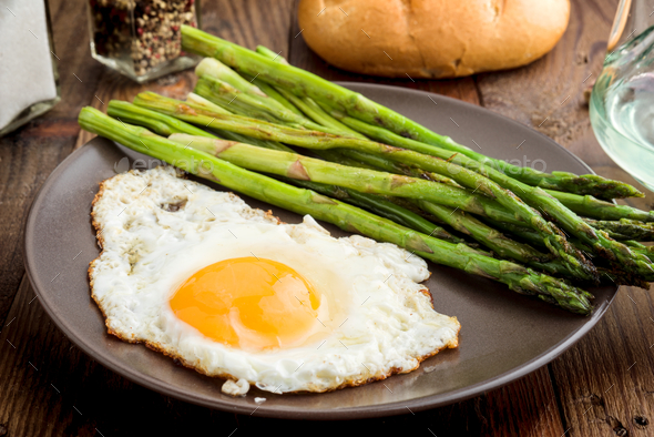 plate with fried egg and asparagus on barbecue on rustic wood - Stock Photo - Images