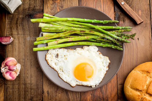 aerial shot of a plate with fried egg and asparagus on barbecue on rustic wood - Stock Photo - Images
