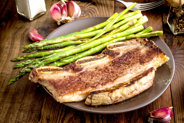 grilled barbecue steak with green asparagus, on rustic wood - Stock Photo - Images