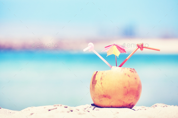 Retro toned picture of a coconut drink on a beach. - Stock Photo - Images
