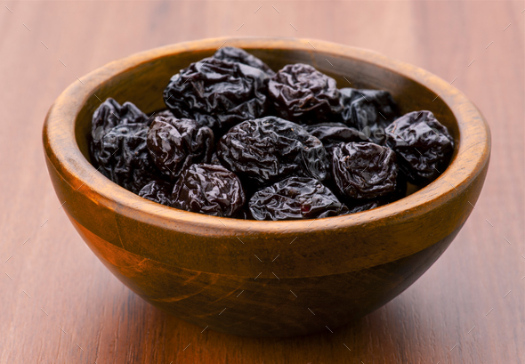 prunes group in wooden bowl - Stock Photo - Images