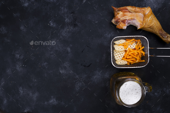 side of a glass of beer, snacks and smoked chicken leg on a black background - Stock Photo - Images