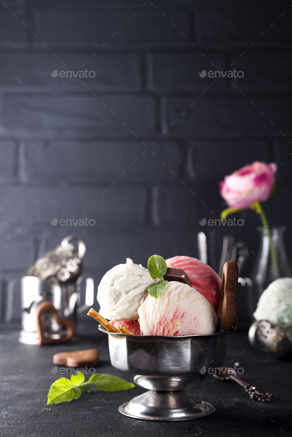 vanilla and pink ice cream in a bowl with frozen berries and waffle cone - Stock Photo - Images