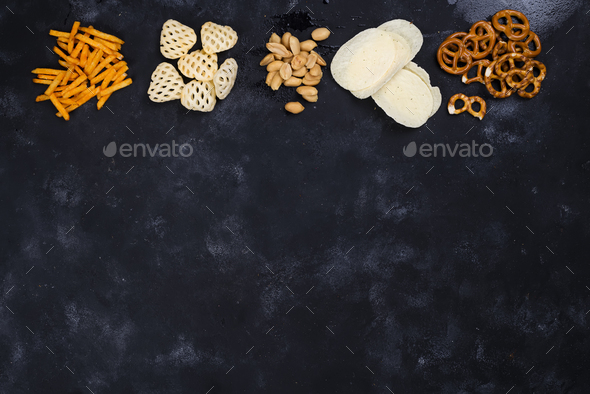 a variety of snacks and snacks for beer on a concrete black table - Stock Photo - Images