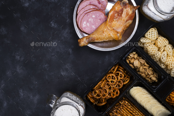 two glasses of beer and snacks, a sausage plate and smoked chicken thighson a concrete black table - Stock Photo - Images