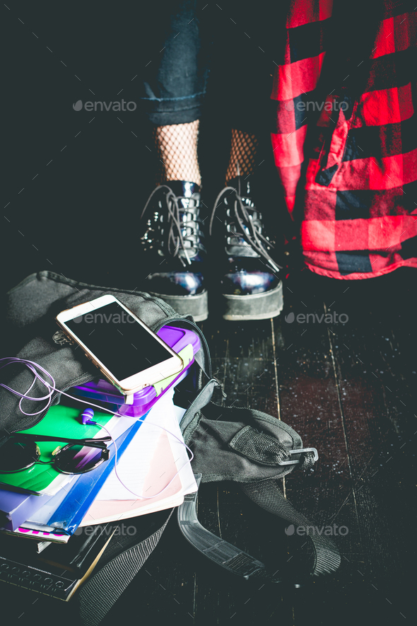 Young alternative girl on the black floor with a school bag - Stock Photo - Images
