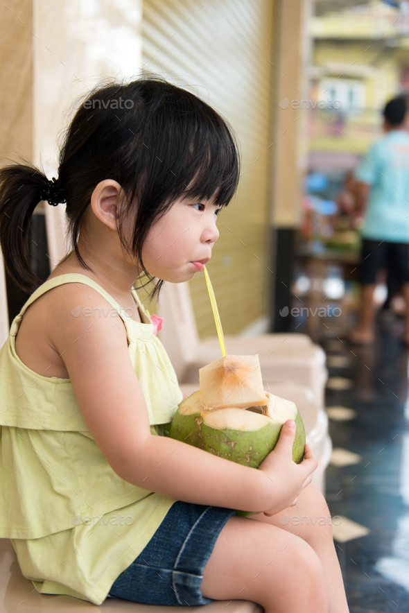 Cute girl drinking coconut water - Stock Photo - Images