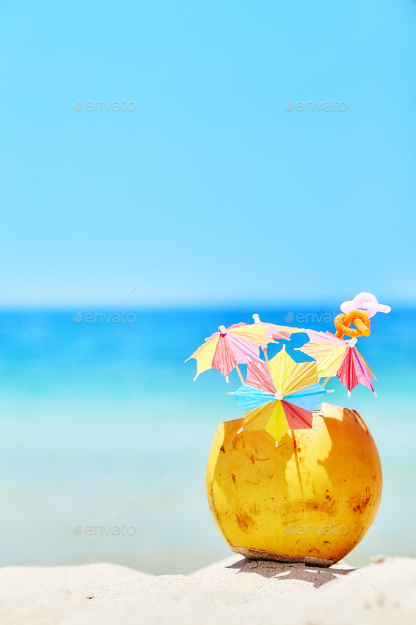 Coconut with colorful umbrellas and straws on a beach. - Stock Photo - Images