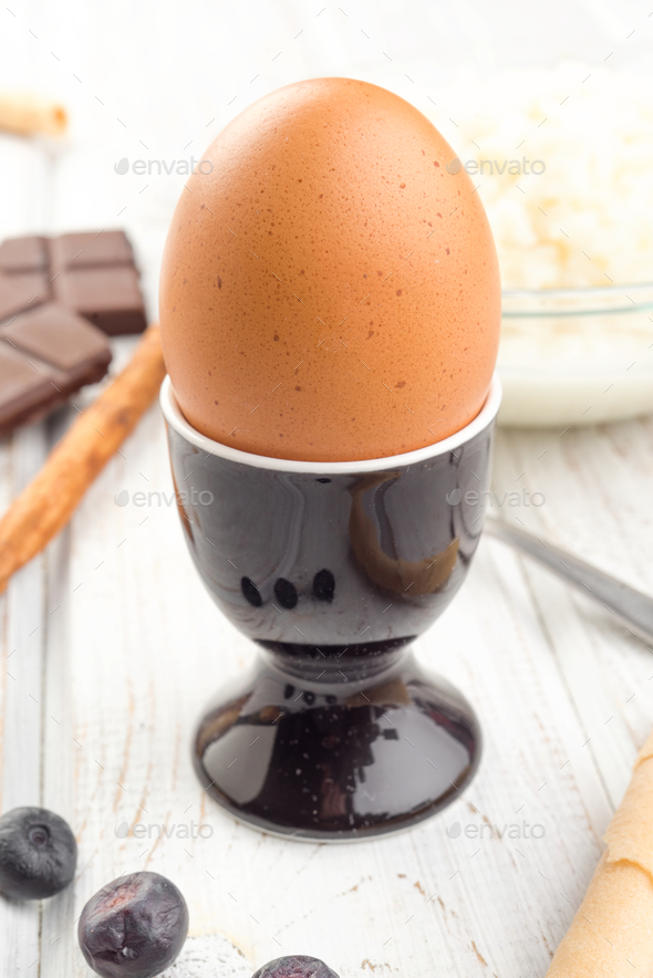 egg in black cup on white wood with chocolate and blueberries - Stock Photo - Images