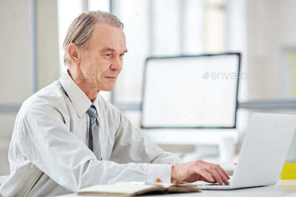 Aged office worker at office - Stock Photo - Images