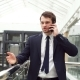 Happy Attractive Young Businessman Walking and Using Mobile Phone Indoors - VideoHive Item for Sale