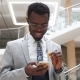 Afroamerican Bearded Businessman Wearing Suit and Glasses Texting on Phone in Modern Office - VideoHive Item for Sale
