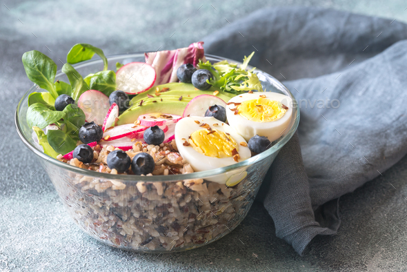 Bowl of wild rice with avocado, egg and lettuce - Stock Photo - Images