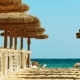 Grass Beach Umbrellas on a Sandy Beach Near the Turquoise Sea - VideoHive Item for Sale