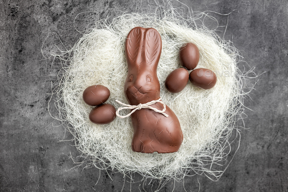Chocolate Easter bunny and eggs in a nest on rustic background - Stock Photo - Images