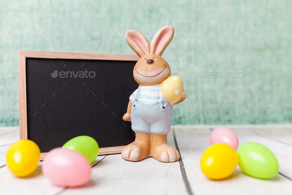 Easter holiday bunny and an empty blackboard - Stock Photo - Images
