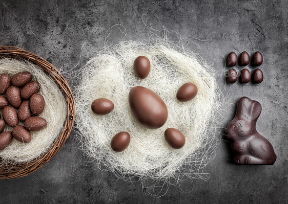 Chocolate Easter eggs in a nest on rustic background - Stock Photo - Images