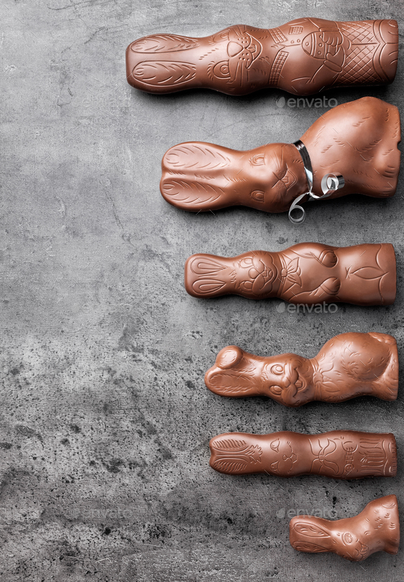 Variety of chocolate Easter bunnies on rustic background - Stock Photo - Images