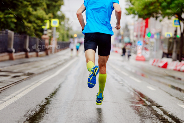 back young runner in yellow compression socks running urban marathon - Stock Photo - Images