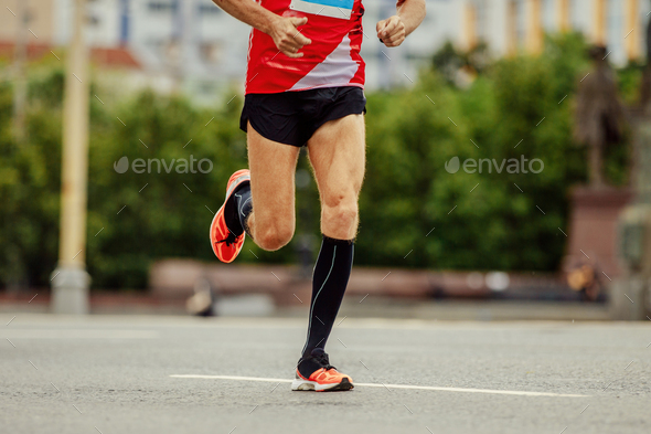 young runner in black compression socks running street in city marathon - Stock Photo - Images