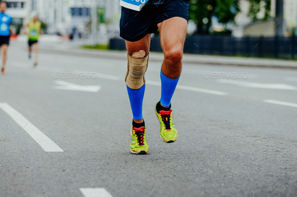 legs runner men in compression calf sleeves and kneepad running in city - Stock Photo - Images