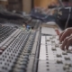 Sound Engineer Is Moving Levers of a Multitrack Mixing Console in the Control Room During a - VideoHive Item for Sale