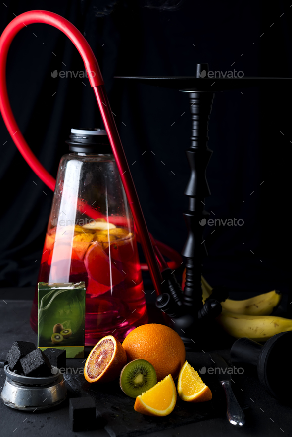 Red hookah with orange slice on a black background - Stock Photo - Images