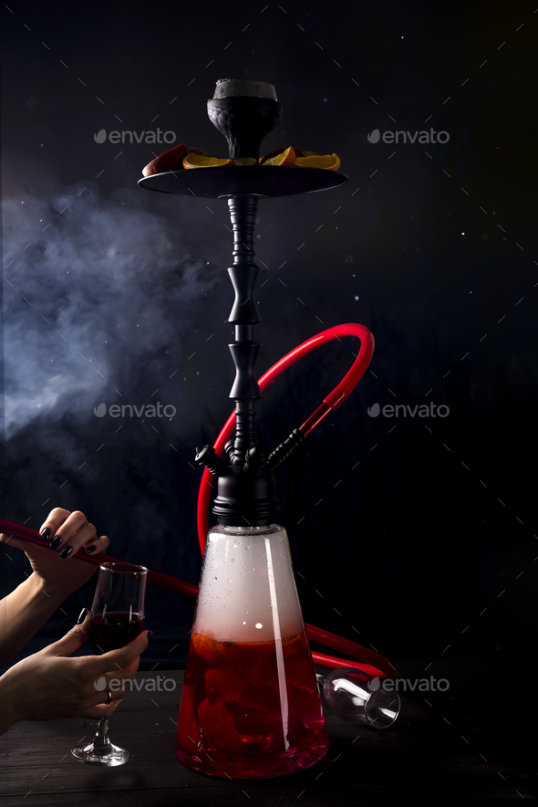 A girl with a glass of red wine smokes a fruit hookah - Stock Photo - Images