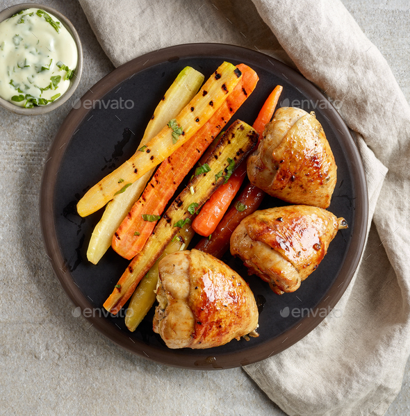 plate of grilled chicken legs and carrots - Stock Photo - Images