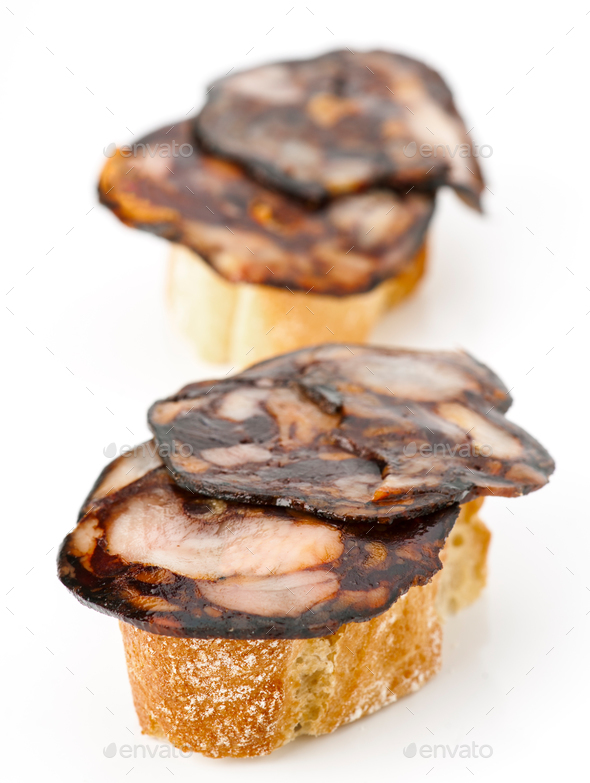 thin slices of Iberian morcilla on bread in white base - Stock Photo - Images