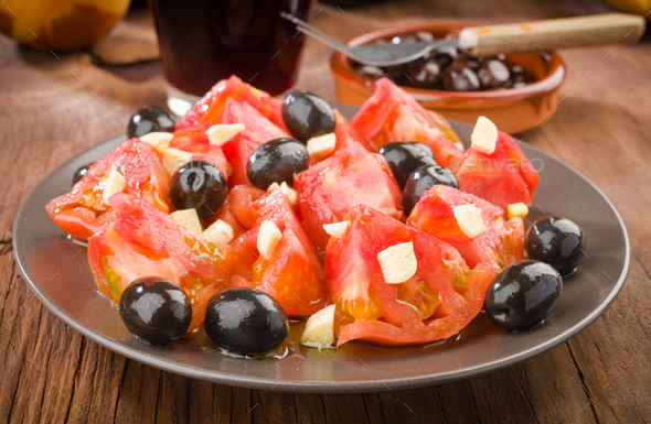homemade salad olives and tomatoes cut with garlic - Stock Photo - Images