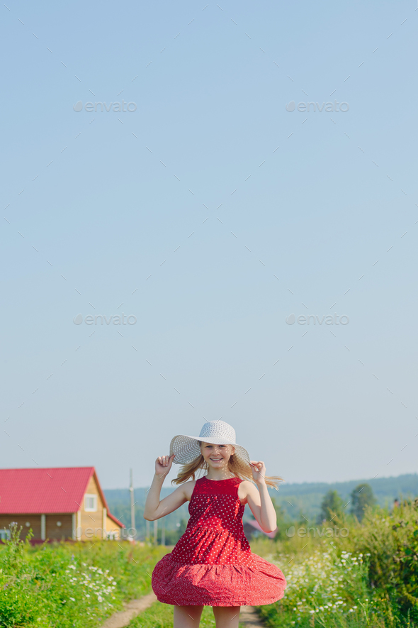 Little girl in red dress and white hat with large brim - Stock Photo - Images